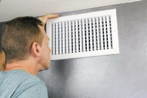 man-looking-into-home-air-vent